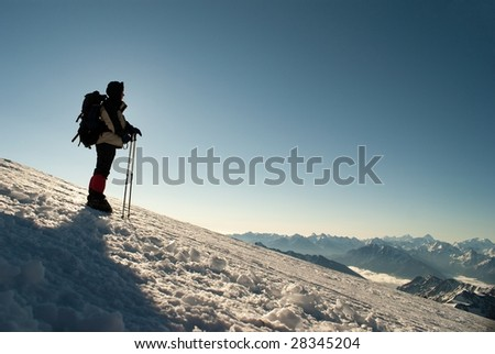 Figure of climber  on a background sunbeams and mountain backbone