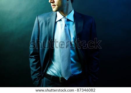Figure of elegant businessman in suit posing in darkness - stock photo