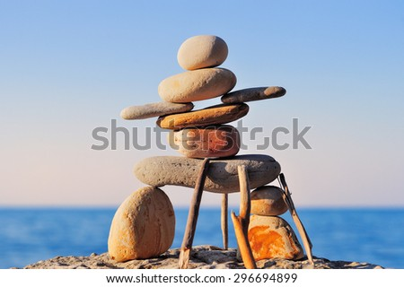Figure of inukshuk on the sea boulder     - stock photo