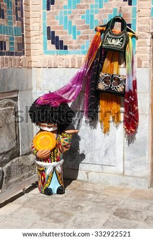 figure of man in traditional Uzbek clothing with pellet, the showcase of the souvenir shop, Uzbekistan - stock photo