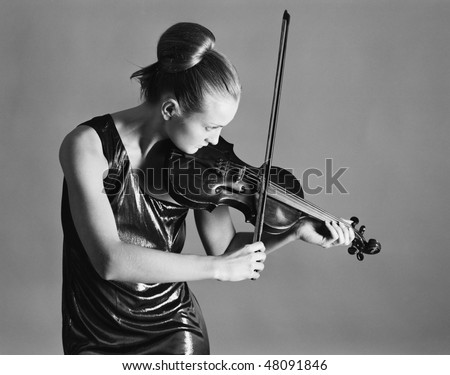 Figure of the young violinist on a grey background - stock photo