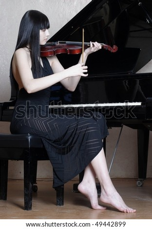 Figure of the young woman in a dark dress with a violin