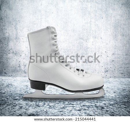 Figure skate on ice floor against concrete wall - stock photo