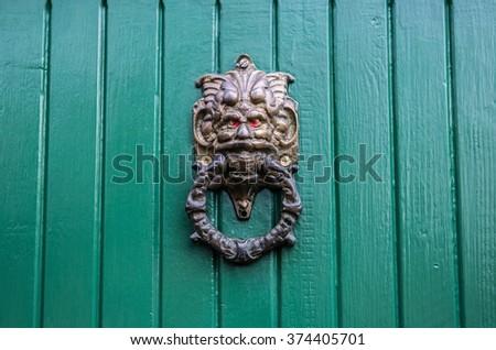 Figured door knocker on green painted wooden door - stock photo