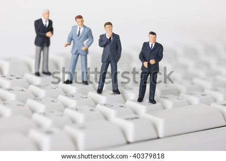 Figures of the businessman on the keyboard.