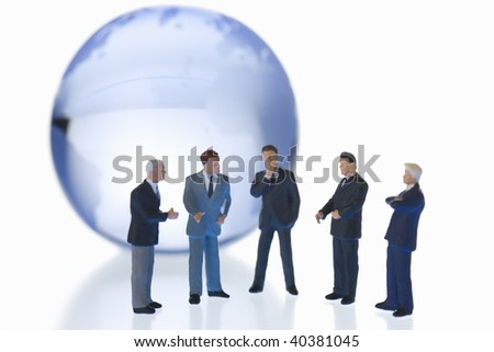 Figures of the businessman who communicates by the side of a globe of glass. - stock photo