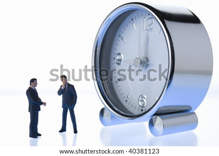 Figures of the businessman who communicates by the side of an alarm clock.