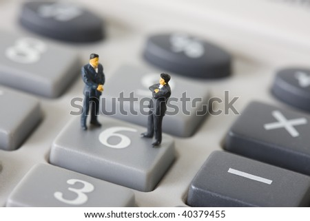 Figures of the businessman who lines up on the calculator.