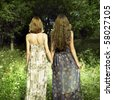 Figures of two romantic girls in green wood - stock photo