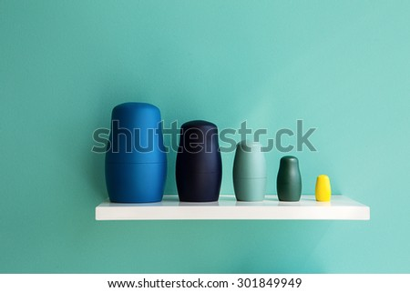 Figures toy matryoshka made in a modern style on a white shelf in one correct geometric series. Detail intrerera. - stock photo