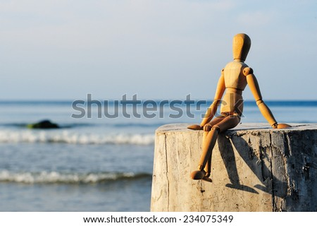 Figurine of wooden man sitting on the stone at the sea