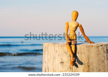 Figurine of wooden woman sitting on the stone at the sea - stock photo