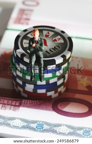Figurine sitting on jetons with euro banknotes, close up - stock photo