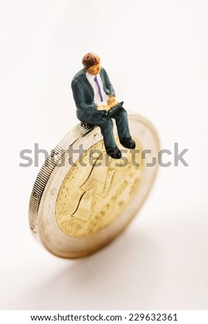 Figurine working on one euro coin - stock photo