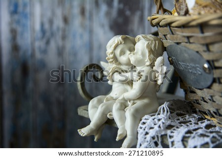 Figurines angels sitting on a bench near the wicker basket. Romance on the background of old boards - stock photo