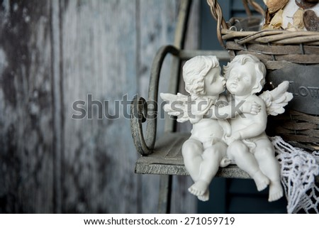 Figurines love angels sitting on a bench. Romance on the background of old boards - stock photo