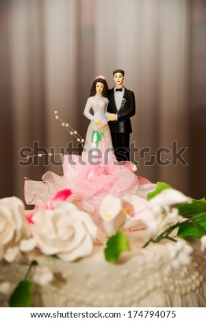 Figurines of bride and groom on cake.
