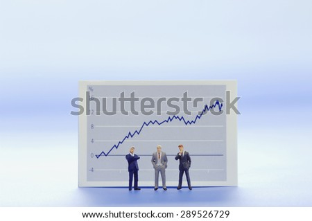 Figurines of businessmen in front of graph - stock photo