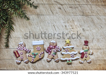 figurines of Christmas cookies on a wooden board with a branch of the Christmas tree. Space for text - stock photo
