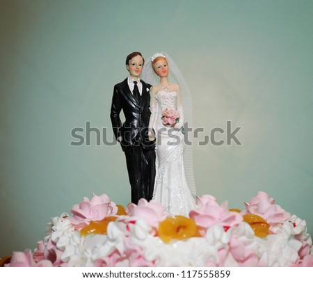 figurines of the bride and groom on a wedding cake - stock photo
