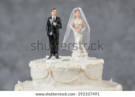 Figurines of the bride and groom on a wedding cake Corny wedding cake that symbolizes the commitment to love one another