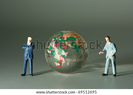 Figurines of two businessmen and glass globe - stock photo