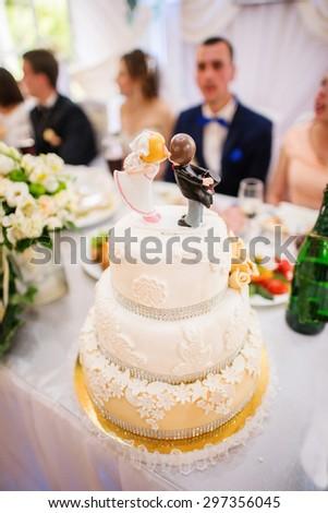 Figurines on top of wedding cake - stock photo
