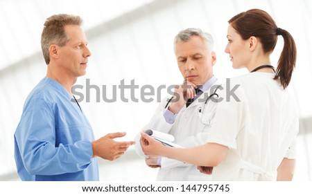 Figuring out the correct medication. Three doctors discussing the report standing close to each other