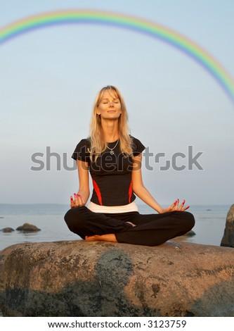 fiit girl meditating at the seashore under rainbow - stock photo