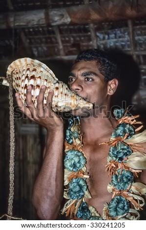 Fiji Islands, Lautoka; 28 january 2001, man in traditional fijian outfit blows in a sea shell - EDITORIAL (FILM SCAN) - stock photo