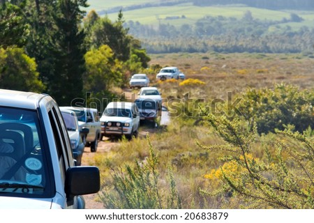 File of cars drives up mountain. Shot in Hottentots-Holland Mountains nature reserve, near Somerset West/Cape Town, Western Cape, South Africa. - stock photo
