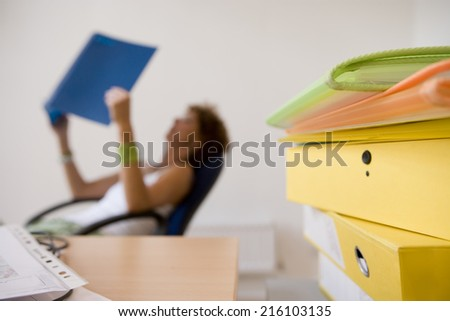 Files by desk, woman reading in background - stock photo