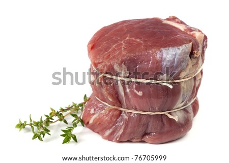 Filet mignon tied with string, ready for cooking.  With thyme. - stock photo