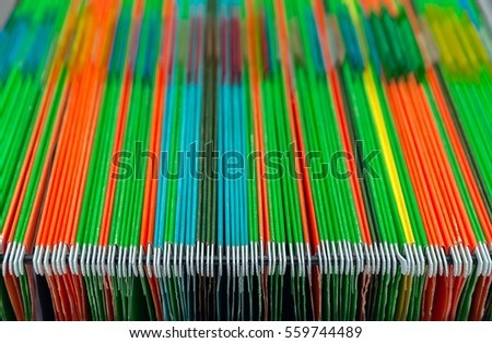 Filing cabinets filled with files of several colors. Abstract background of colorful hanging file folders in drawer. Stock photo