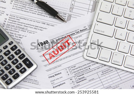 Filing taxes online using a computer and being audited - stock photo