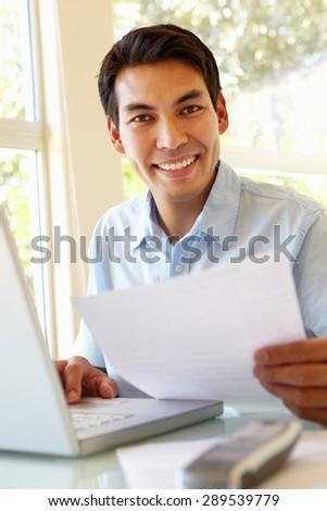 Filipino man working at home - stock photo
