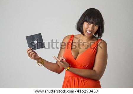 Filipino woman wearing a low cut orange dress holding a five inch floppy drive - stock photo
