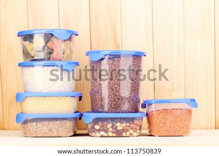 Filled plastic containers on wooden background - stock photo