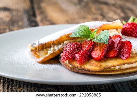 filled with homemade pancakes with strawberries and maple syrup