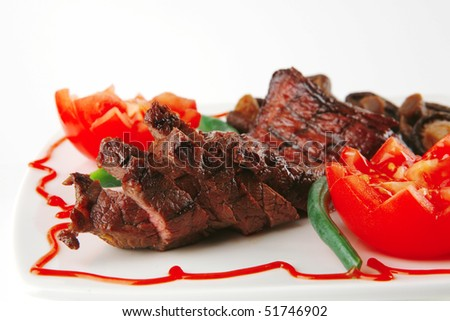 fillet mignon served on a white plate with tomatoes - stock photo