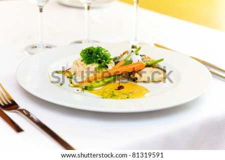 Fillet of cod baked with Paris butter served with sous-vide vegetables and Sauce Hollandaise - stock photo