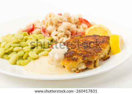 Fillet of Cod breaded in crumbs and spices and baked to golden brown on plate with lima beans and pasta salad.  White background with copy space. - stock photo