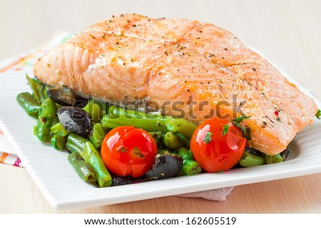 Fillet of red fish salmon with green beans, tomatoes and black olives, tasty diet dinner - stock photo