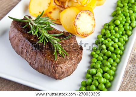 Fillet with fried potatoes and green pea - stock photo