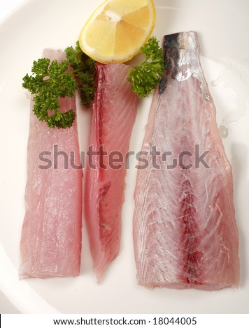 fillets of Spanish narrow-barred mackerel (also known as kingfish) on a plate viewed from above. - stock photo