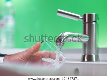Fillig glass with drinkable water - stock photo