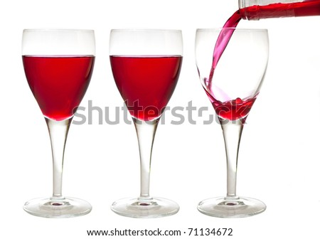 Filling a crystal glass with cherry liqueur drink while two other already filled isolated on white background - stock photo
