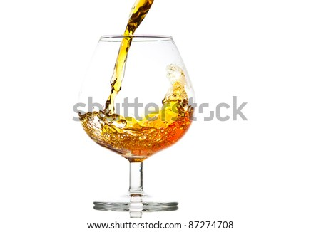 filling a glass of brandy, close-up - stock photo