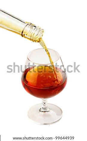 Filling a glass of brandy isolated on white background
