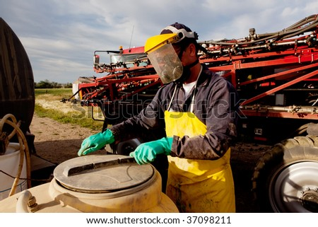 Filling a high clearance sprayer with chemical and water with proper safety equipment - stock photo